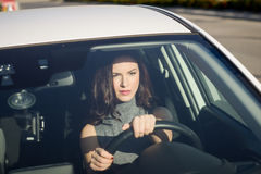Brunette woman driving a white car in urban background Royalty Free Stock Image
