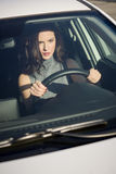 Brunette woman driving a white car in urban background Stock Photography