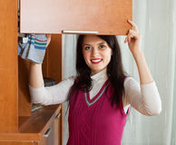 Brunette woman dusting wooden furiture Royalty Free Stock Photography