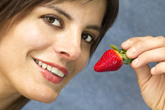 Brunette woman  eating strawberry fruit Stock Photography