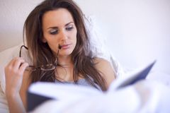 Brunette Woman Engrossed in Her Reading. Brunette woman engrossed in reading a book while in her room Stock Photography