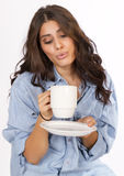 Brunette Woman Enjoys Morning Coffee. Young Latino female cools her fresh morning cup of coffee Royalty Free Stock Photo