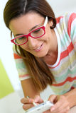 Brunette woman with eyeglasses using smartphone with a pen Royalty Free Stock Images