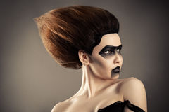 Brunette woman with fashion hairstyle and creative dark makeup stock photography