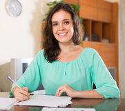 Brunette woman filling papers at home Royalty Free Stock Image