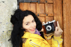 Brunette woman holding photo camera. Beautiful brunette photographer holding camera in front of an wooden door, taking pictures smiling Stock Image