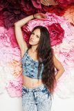 Brunette woman on floral background. Portrait of beautiful young brunette woman with long natural hair posing on flower background, wearing jeans, natural looks Royalty Free Stock Images