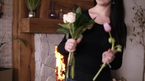 Brunette woman florist creating beautiful bouquet in flower studio or home. Owner in floral design studio, making stock footage