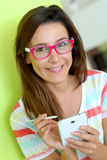 Brunette woman with a funny look writing on smartphone. Brunette girl with eyeglasses using smartphone stock images