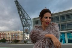 Brunette woman with fur coat portrait standing outside, with a port crane in the background royalty free stock image