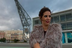 Brunette woman with fur coat portrait standing outside, with a port crane in the background stock photos