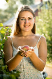 Brunette woman at garden holding ripe apple at hands Stock Photo
