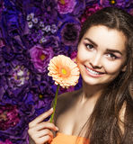 Brunette woman with a gentle make-up that looks at the camera while holding flower near the face on a floral background. Portrait of a beautiful brunette woman Stock Photography
