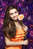 Brunette woman with a gentle make-up that looks at the camera while holding flower near the face on a floral background. Portrait of a beautiful brunette woman Stock Photos
