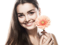 Brunette woman with a gentle make-up that looks at the camera while holding flower near the face on a isolated. Portrait of a beautiful brunette woman with a Stock Images