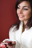 Brunette Woman with gift. A smiling Brunette woman giving gift Stock Image