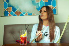 Brunette woman with green eyes smokes shisha Royalty Free Stock Images