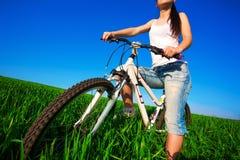 Brunette woman in a green field on a bike Royalty Free Stock Image