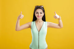 Brunette woman in green swimsuit on yellow background. summer sexy girl in turquoise bodysuit showing thumbs up Royalty Free Stock Images