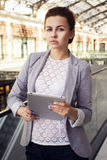 Brunette woman in grey jacket, dark trousers and white blouse with tablet outdoors Stock Image
