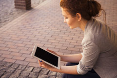 Brunette woman in grey jacket, dark trousers and white blouse with tablet outdoors. Copy Space Stock Image