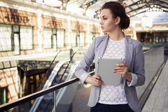 Brunette woman in grey jacket, dark trousers and white blouse with tablet outdoors. Copy Space Stock Images