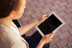 Brunette woman in grey jacket, dark trousers and white blouse with tablet outdoors. Copy Space Stock Photography