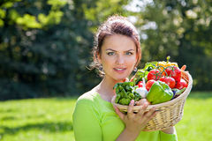 Brunette woman with groceries in wicker basket Royalty Free Stock Images
