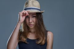Beautiful woman in hat and black shirt is posing stylishly isolated on gray background in a studio close up stock photography