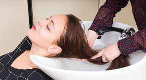 Brunette Woman Having Hair Washed in Salon Stock Image