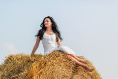 Brunette woman on hay bale Stock Photos
