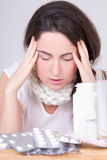 Brunette woman with headache and pills on the table Royalty Free Stock Photo