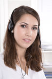Brunette woman at helpdesk wearing headset Stock Image