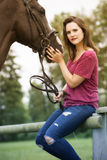 Brunette woman and her horse on farmland stock photo