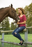 Brunette woman and her horse on farmland stock image