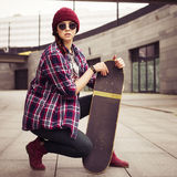 Brunette woman in hipster outfit sitting on a scateboard on the street. Toned image Royalty Free Stock Photography
