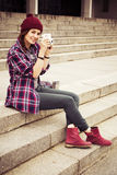 Brunette woman in hipster outfit sitting on steps and photographing on retro camera on the street. Toned image Royalty Free Stock Photography