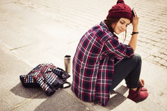 Brunette woman in hipster outfit sitting on steps on the street. Toned image. Copy Space Royalty Free Stock Images