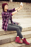 Brunette woman in hipster outfit sitting on steps and taking selfie on retro camera on the street. Toned image Royalty Free Stock Photography