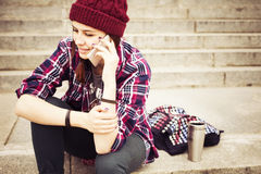 Brunette woman in hipster outfit sitting on steps and talking on the phone on the street. Toned image. Copy Space Stock Photos