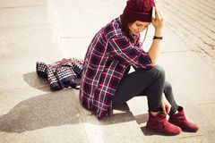 Brunette woman in hipster outfit sitting on steps and talking on the phone on the street. Toned image. Copy Space Stock Images
