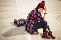Brunette woman in hipster outfit sitting on steps and talking on the phone on the street. Toned image. Copy Space Royalty Free Stock Photography