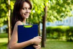 Brunette woman holding blue tablet Stock Photos