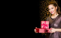 Brunette woman holding Christmas gifts. Stock Photos