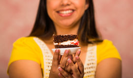 Brunette woman holding delicious piece of chocolate cake with cream filling, big smile and ready to take a bite, pastry Royalty Free Stock Photography