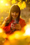 Brunette woman holding evaporating cup of tea at autumn park Stock Photo