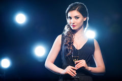 Brunette woman holding glass of champagne and looking at camera Royalty Free Stock Images