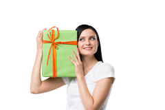 A brunette woman is holding a green gift box. Stock Photos
