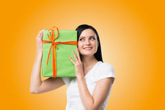 A brunette woman is holding a green gift box. Royalty Free Stock Photography