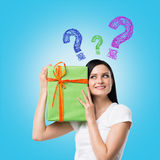 A brunette woman is holding a green gift box and question mark as a concept of gift uncertainty. Stock Photography